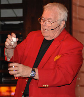 Corporate entertainer Al Lampkin cracking an egg as part of a magic trick before a live audience